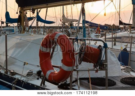Closeup of Orange Lifebuoy and Rolled Rope on Sailing Boat: Dock Seaside at Sunset