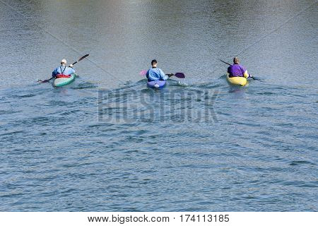 Three rowers with canoe recreate in a lake