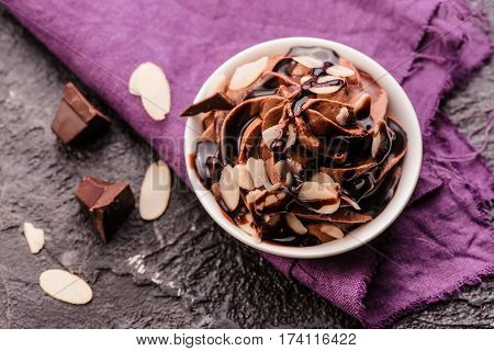 Chocolate mousse with chocolate sauce and chocolate pieces, almond slices in a glasses on a vintage background. Top view.