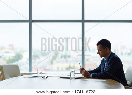 Profile view of young business man sitting alone against window at large table, looking anxious and nervous fiddling with pen while waiting for his partner being late for meeting