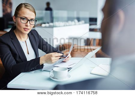 Beautiful lady executive leading negotiations over contract with business partner, explaining details of deal and looking persuasively at man in front, both seated in lounge area of modern restaurant