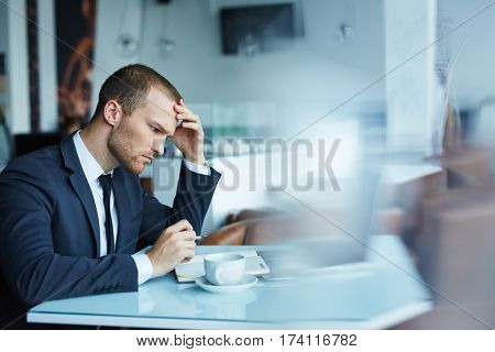 Young handsome man wearing formal attire working with laptop in empty hall of modern restaurant during coffee break, looking puzzled and thinking hard trying to solve some important matter