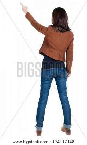 Back view of  pointing woman. beautiful brunette  girl in brown jacket. Rear view people collection.  backside view of person.  Isolated over white background.