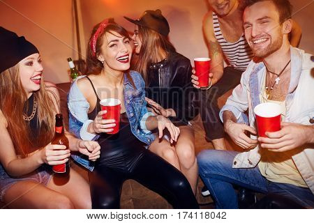 Group of drunk young people chilling at house party, laughing and drinking beer sitting on couch