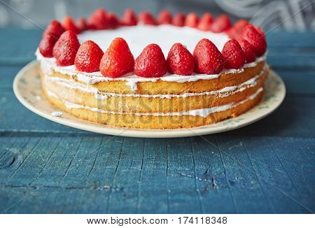 Closeup of delicious simple biscuit cake decorated with fresh ripe strawberries on top and white icing between layers standing on rustic wooden table
