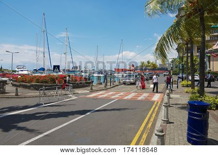 PORT LOUIS, MAURITIUS - NOVEMBER 29, 2012: Unidentified people walk by the street in Caudan waterfront area of Port Louis, Mauritius.