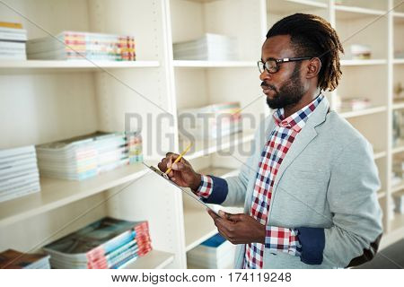Profile view of concentrated bearded businessman with short dreadlocks standing at bookshelves and taking notes with pencil