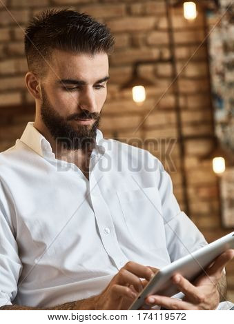Young trendy bearded man browsing internet on tablet at loft home. Concentration on face.