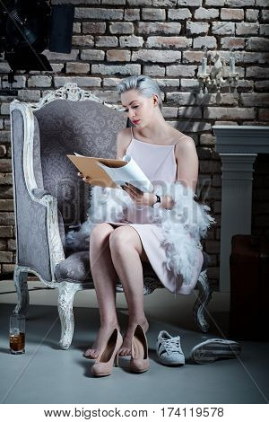 Actress in retro style sitting in armchair, reading script before filming.