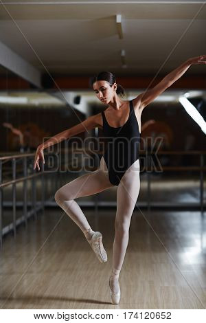 Full body shot of graceful Hispanic ballerina making elegant move during ballet practice in dim dance studio