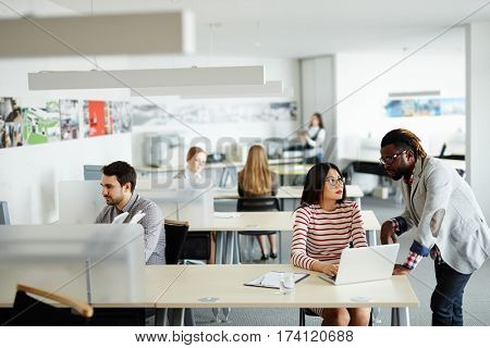 Interior of busy open plan office: male and female workers sitting at their desks, Afro-American superior discussing business project with pretty Asian employee