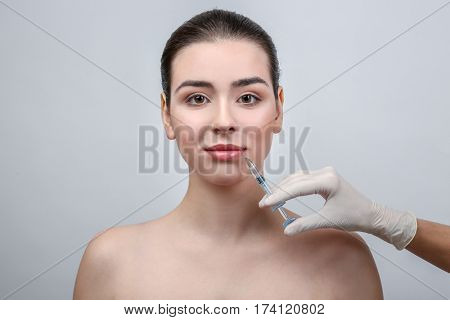 Beautiful young woman receiving filler injection in face, on light background