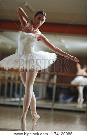 Portrait of graceful ballerina wearing white tutu dancing in half-lit ballet studio practicing for stage performance