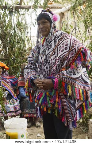 Native Peruvian man wearing a handwoven poncho and a chollo - knitted hat with earflaps attending his daughter wedding ceremony. Next to him is a bucket with chicha - local beer derived from maize. October 22 2012 Amaru, Peru