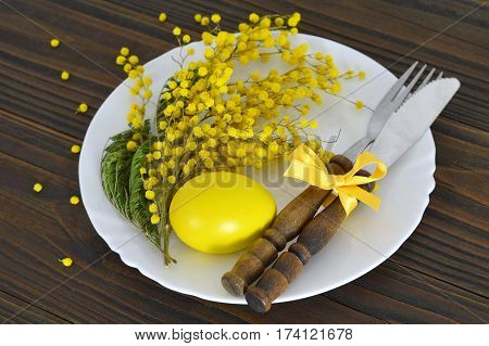 Easter table decoration: Easter egg, mimosa and silverware on the plate