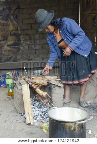 Native Peruvian woman preparing guinea pigs over fire. Guinea pigs are special dish in Peru prepared for weddings and religious ceremonies. October 22 2012