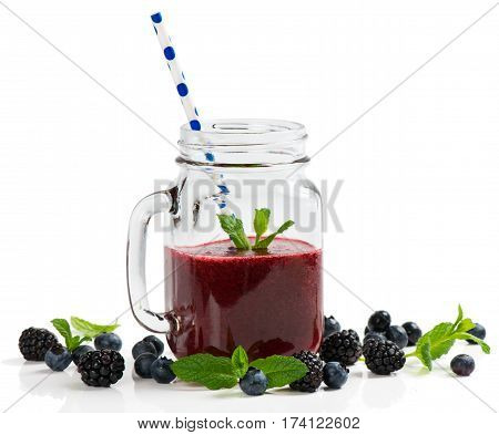 Smoothie of summer berries (blueberry and blackberry) in mason jars with straws isolated on white background.