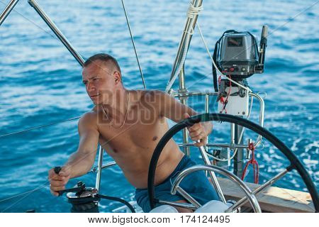 Skipper man at the helm controls of a sailing yacht during sea boats race.