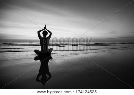 Woman doing meditation near the ocean beach. Black and white silhouette.