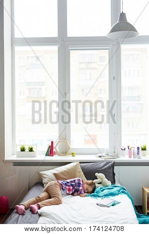 Tired little girl taking a nap on her comfortable bed in bright room with large plastic window up to ceiling