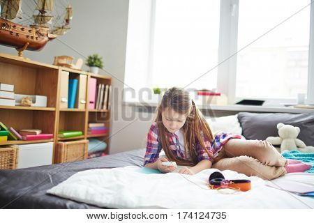 Pretty teen girl texting on her smartphone while resting on bed after classes in her stylish cozy room