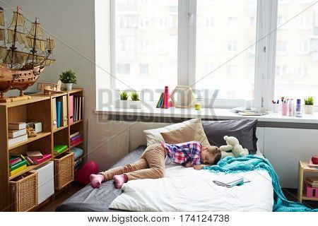 Tired schoolgirl sleeping in stylish cozy bedroom with large window, modern furniture and big ship model on shelf