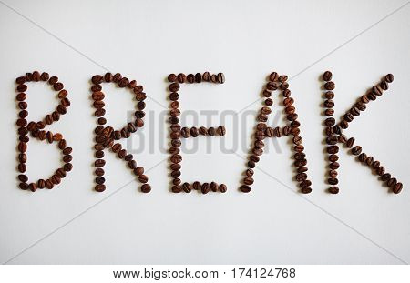 Creative coffee break concept: Top view of word Break laid out on white table with rich roasted coffee beans in large letters