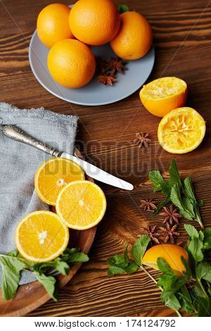 Directly above view of rustic wooden kitchen table with fruits and spices on it, all set for making mullet wine: fresh ripe oranges cut in half, mint and star anise scattered in elegant assortment