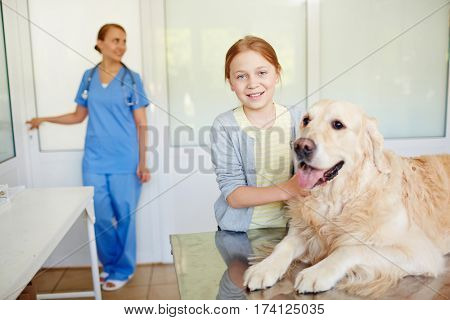 Small red-haired owner standing next to her dog resting on examination table after checkup and smiling at camera brightly