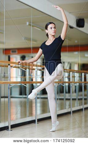 Full body shot of graceful Latin ballerina standing practicing moves against bar during ballet lesson in dance studio