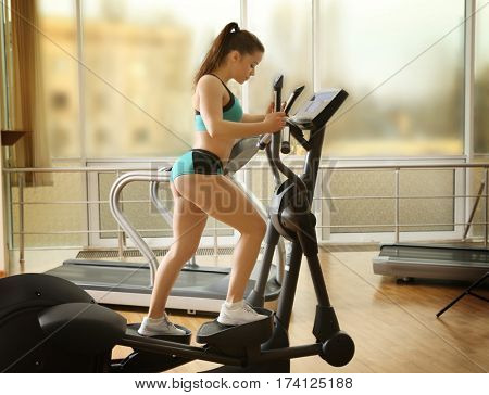 Young woman on elliptical trainer in gym