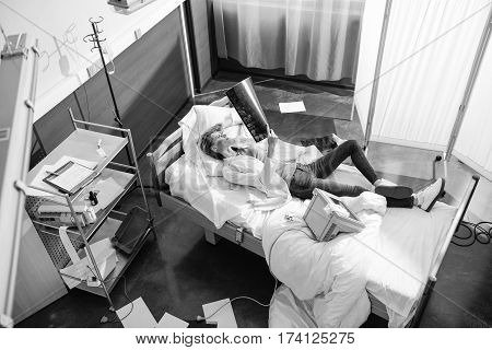 high angle view of doctor examining x-ray picture on bed black and white photo