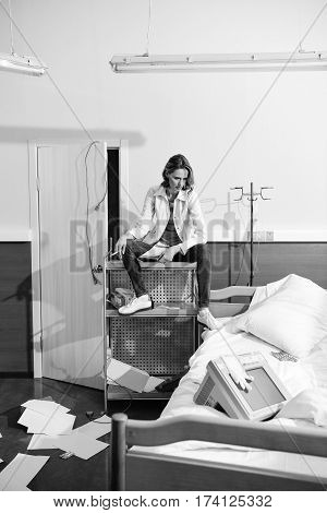 doctor in uniform sitting on medical equipment in hospital chamber black and white photo