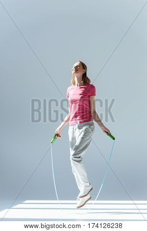 side view of sporty woman exercising with skipping rope on grey