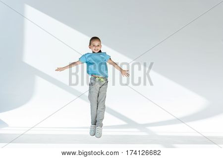 Happy little girl in sportswear jumping with open arms and smiling at camera