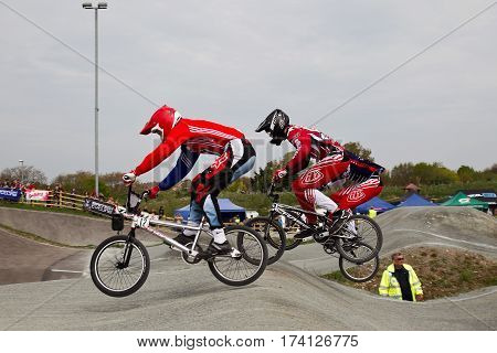 GRAVESEND, UK - APRIL 12: Riders competing in the mens class of the UK National BMX champs at the Kent cyclopark negotiate the rollers section during the final race on April 12, 2014 in Gravesend