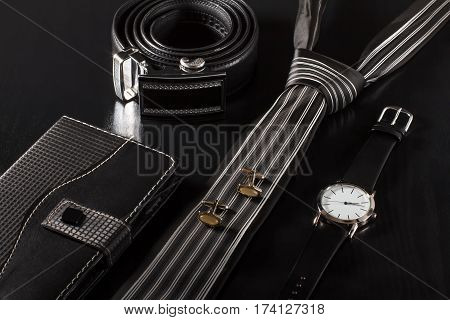 Notebook in leather cover tie cufflinks leather belt with metal buckle watch with a leather strap on a black background