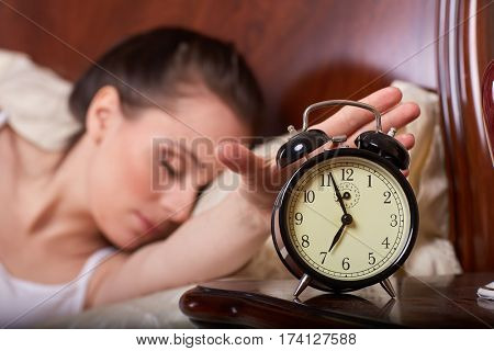 Young sleeping woman and alarm clock in the bedroom.  Selective focus on a alarm clock.