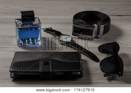 Man perfume watch with a leather strap leather belt with metal buckle notebook in leather cover black sunglasses on a gray wooden background