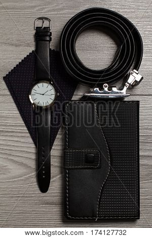 Leather belt with metal buckle watch with a leather strap silk handkerchief notebook in leather cover on a gray wooden background
