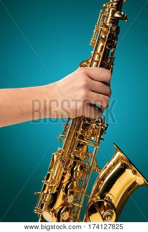 Saxophone - Golden alto saxophone classical instrument on blue and male hand