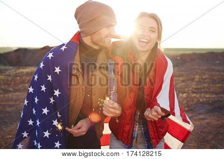 Portrait of  happy couple wearing fashionable tourist clothes laughing and  holding sparklers, both wrapped in American flag against sunlight in mountains