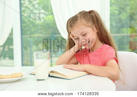 Little girl sitting at table with glass of milk and reading book