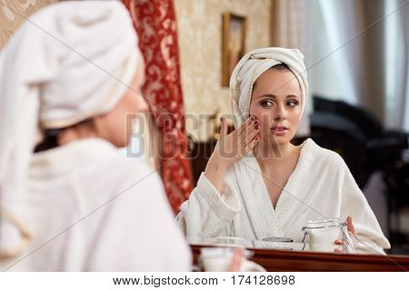 Young woman with cosmetic cream sits before a house  dressing table.Concept body care.
