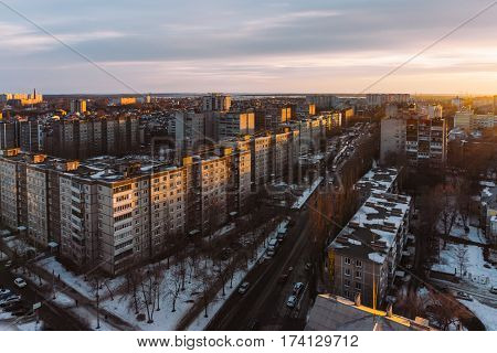Aerial panoramic evening cityscape from rooftop of Voronezh. Houses, sunset, sky, clouds, road or prospect, dramatic view in warm tones with copyspace