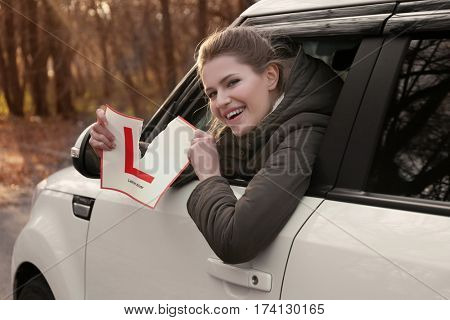 Young woman tearing learner driver sign while looking out of car window