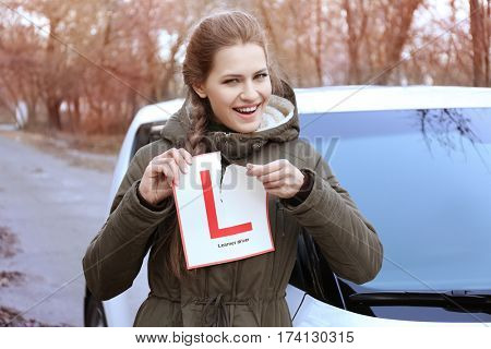 Happy young woman tearing learner driver sign while standing near car outdoors