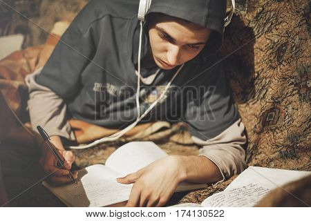 Teenage student guy studying lying on the sofa at home listening to music