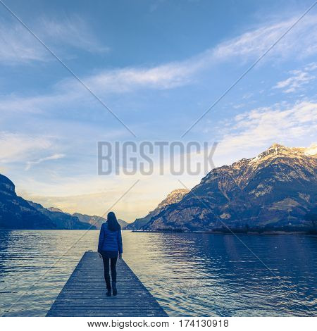 Woman goes on a wooden pier. Lake between the mountain ranges. Mountain landscape .
