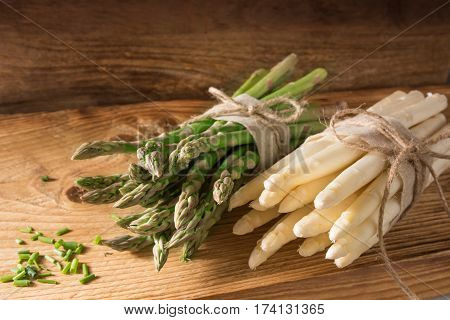 Fresh green and white asparagus with chopped parsley on rustic wood